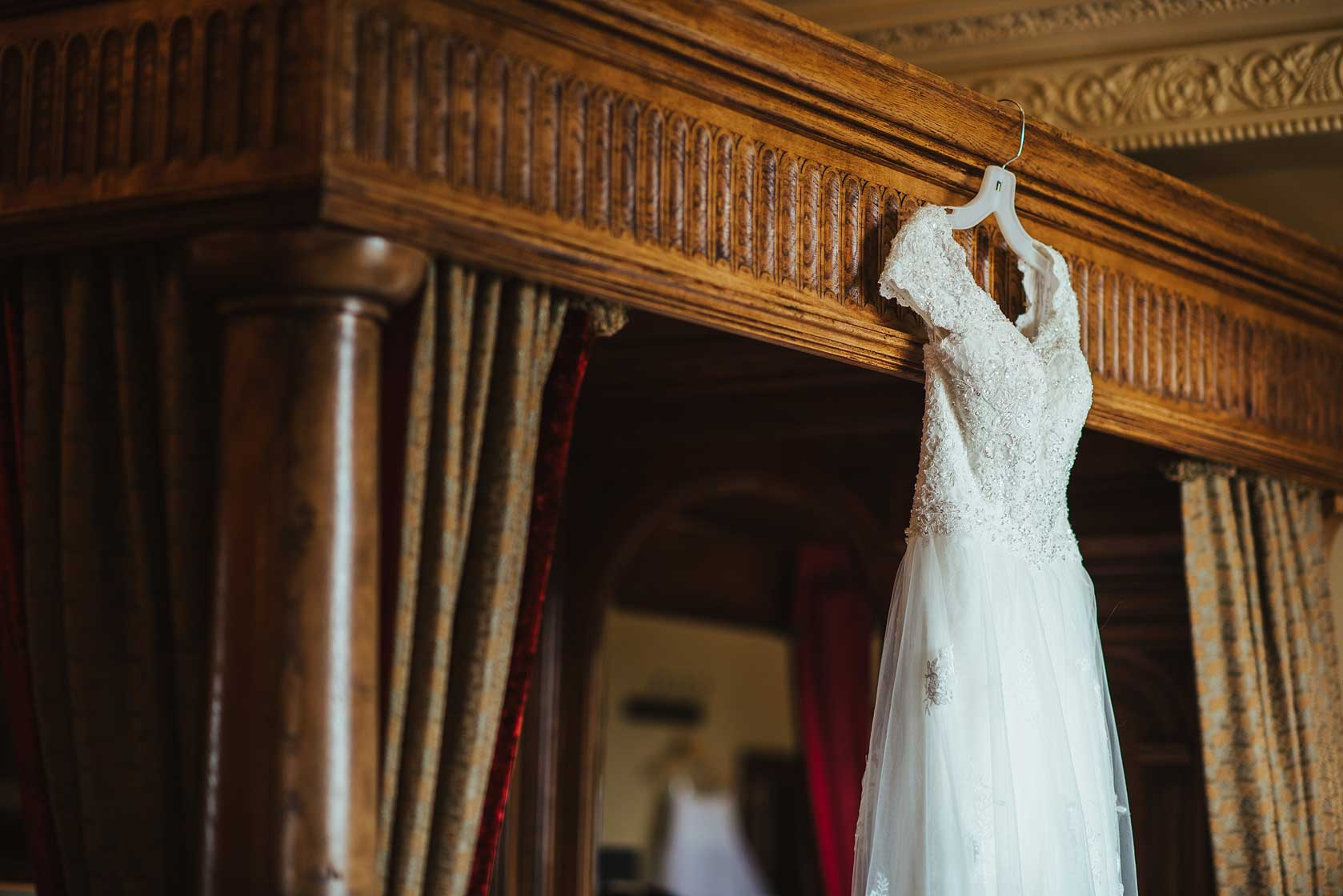 Wedding dress hanging on a four poster bed