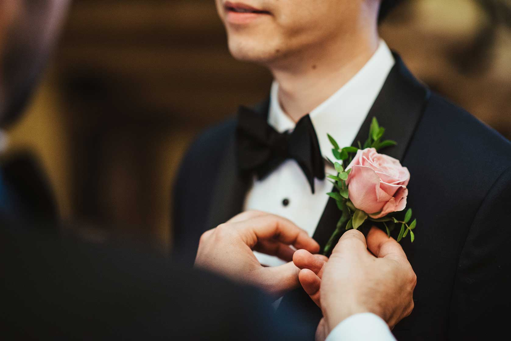 Groom at Stoke Park has wedding buttonhole fitted