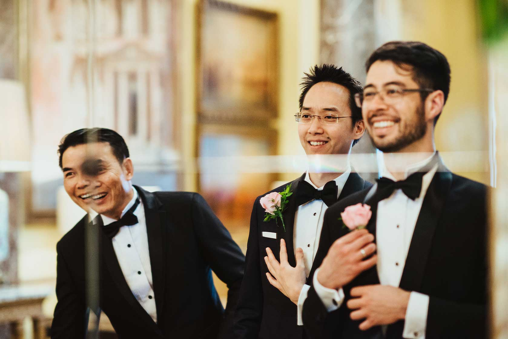 Groom and best man check themselves in a mirror