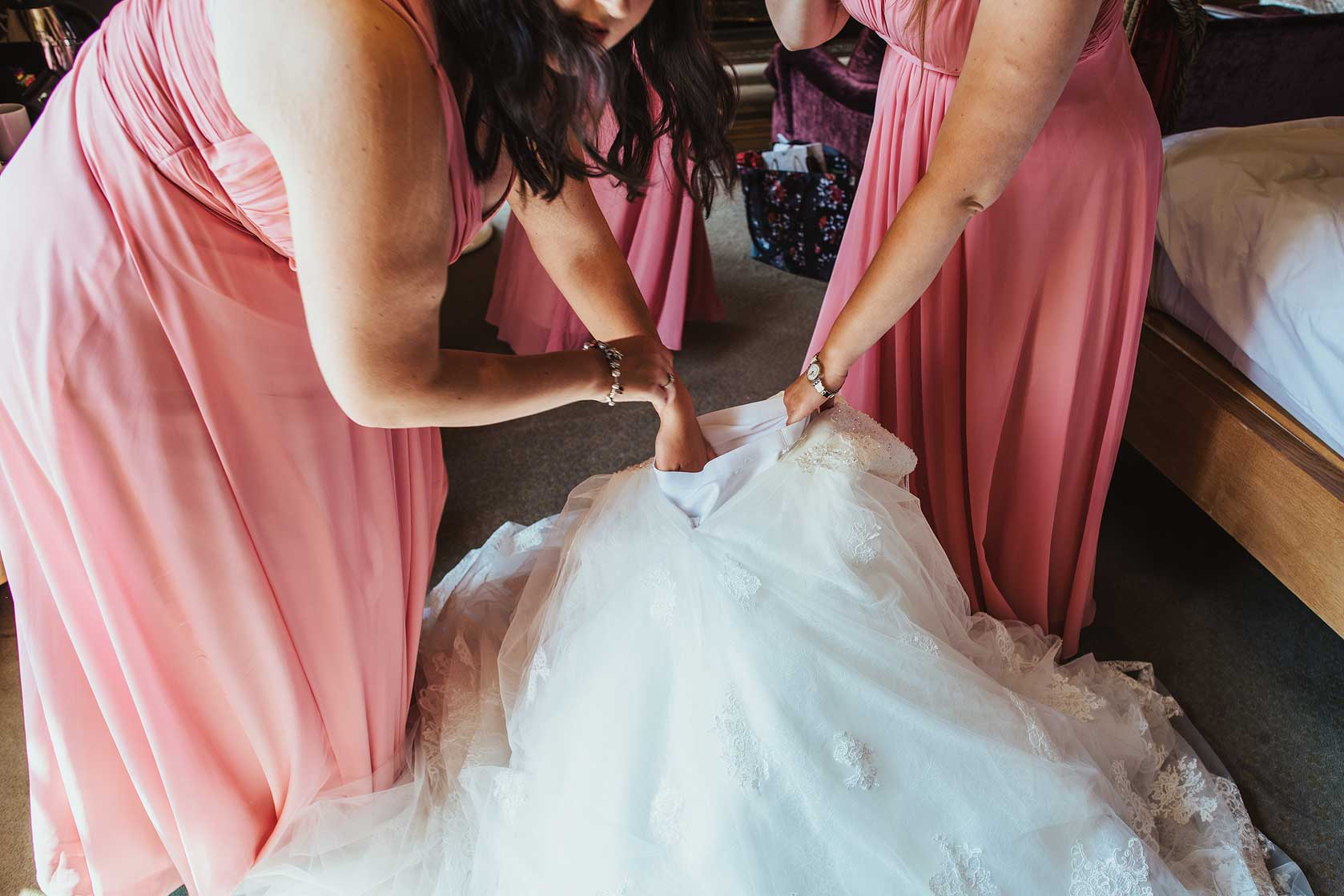 Bridesmaids prepare the wedding dress