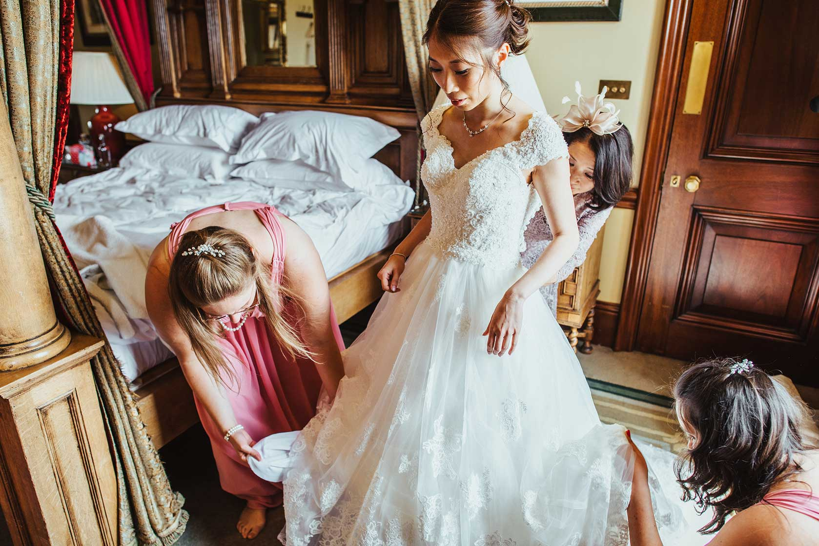A bride is fitted into her wedding dress at Stoke Park