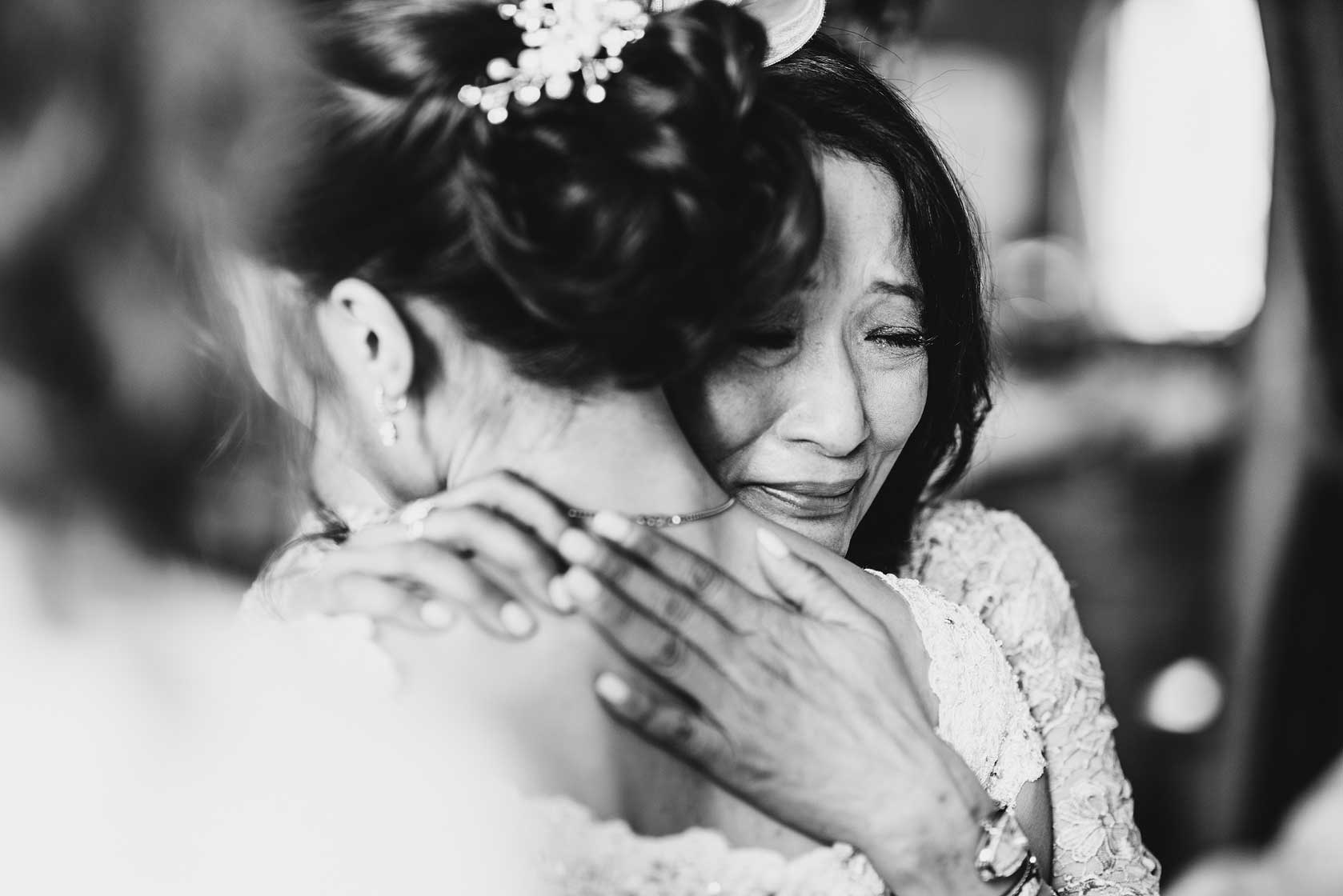 Mother of bride crying and hugging her daughter
